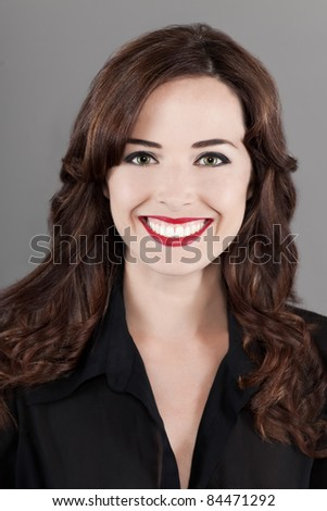 Closeup portrait of a beautiful happy brown haired woman toothy smiling isolated on gray background