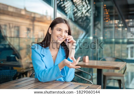 Closeup portrait of a beautiful happy woman talking at phone happy smiling looking at camera in her home kitchen, on a balcony at home near window or in a coffee shop, trendy cafe wearing blue suit. stock photo