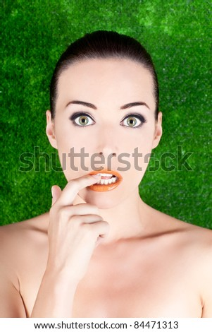 Closeup portrait of a beautiful nervous woman biting her finger isolated on green - stock photo