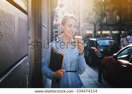 Closeup portrait of a beautiful smiling business woman walking and drinking coffee