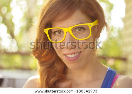 Closeup portrait of a beautiful smiling hipster redhead girl wearing big yellow glasses, selective focus, lens flare