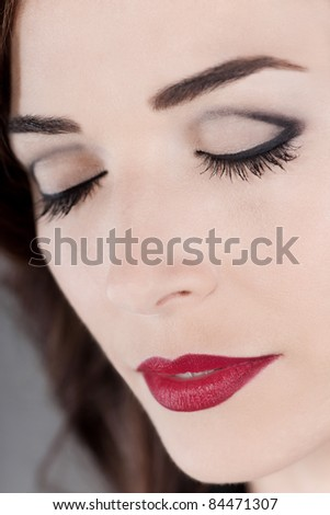 Closeup portrait of a beautiful woman eyes closed and red lips close up
