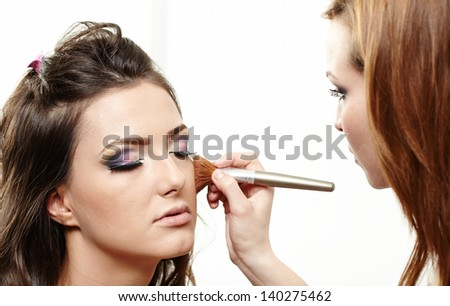 Closeup portrait of a beautiful woman having makeup applied by makeup artist
