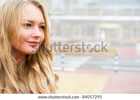 Closeup portrait of a beautiful woman in the city at summer time with modern building at the background