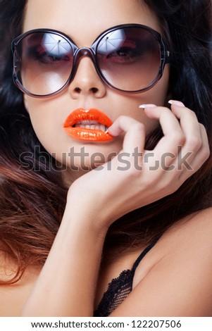 Closeup portrait of a beautiful woman wearing trendy sunglasses