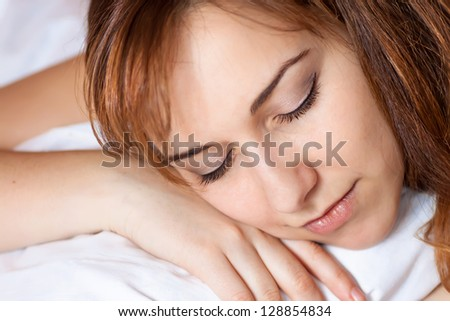 Closeup portrait of a beautiful young lady sleeps on the bed.