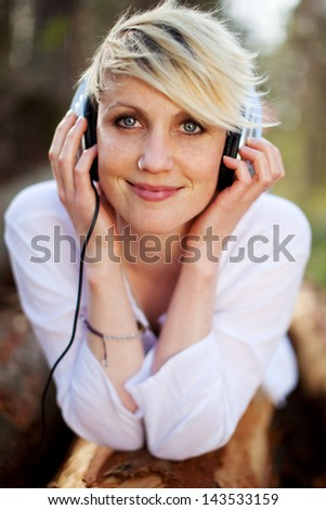 Closeup portrait of a beautiful young woman with headphones lying on log