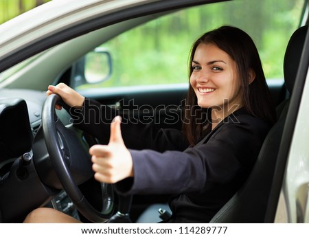 Closeup portrait of a beautiful young woman with thumbs up in her new car