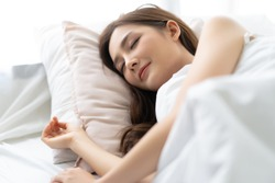 Closeup portrait of a calm young pretty Asian woman sleeping in her bed and relaxing in the morning. Lady enjoying sweet dreams and enough rest concept