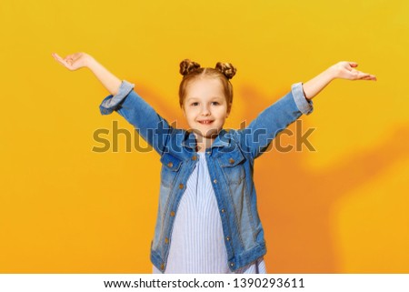 Closeup portrait of a charming little kid girl on a yellow background. The child raised his hands palm up. #1390293611