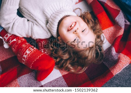 Closeup portrait of a curly-haired boy, the boy lies on a red plaid on the floor in a sweater smiling without teeth looking at the frame. #1502139362