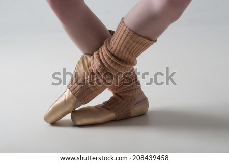 Closeup portrait of a dancer, legs in ballet shoes and long socks dancing in pointe isolated on white background