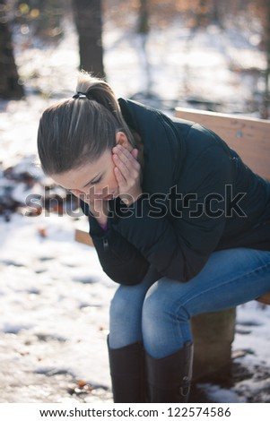 Closeup portrait of a depressed young woman sitting on a bench outdoors on a cold winter day