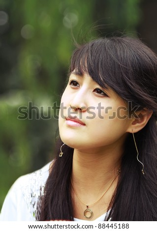 Closeup portrait of a fashion asian girl, a Chinese teenager looking up happily in peaceful green park
