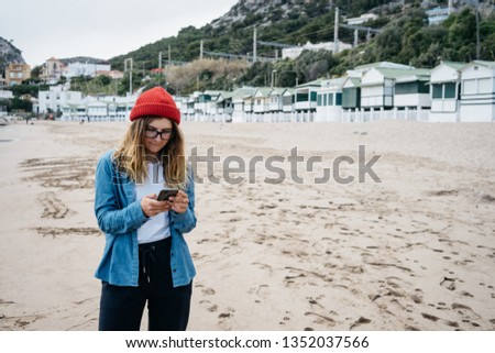 closeup portrait of a female  using mobile phone, beach on background. young millennial texts on vacation. women uses mobile app. space for your text or logo #1352037566