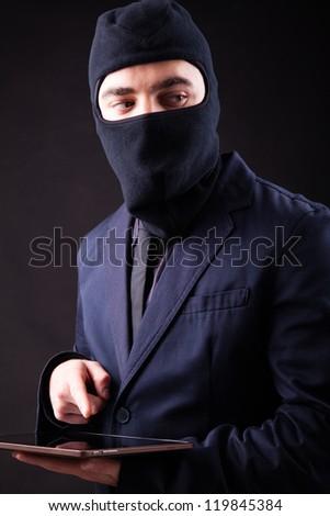 Closeup portrait of a hacker stealing data from digital tablet