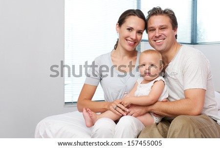 Closeup portrait of a happy mother and father sitting at home with cute baby