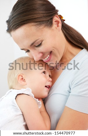 Closeup portrait of a happy mother hugging cute baby against white background