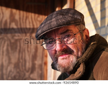 Closeup portrait of a happy smiling senior man with a hat outdoors