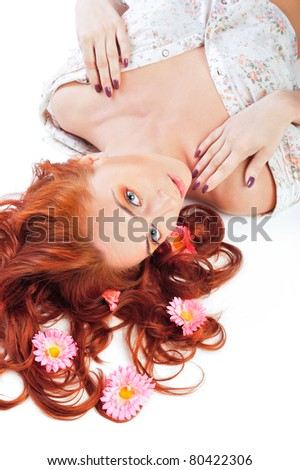 Closeup portrait of a happy young lady with flowers in her hair lying on white background. Beautician and hairdresser advertisement