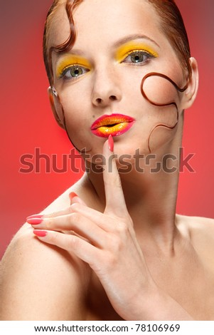 closeup portrait of a lovely redhead girl with creative makeup and her finger near lips over red background