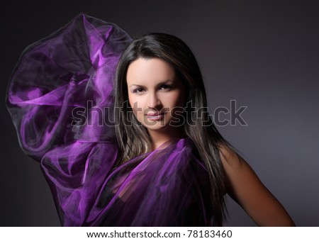 Closeup portrait of a lovely young female model with a purple dress posing against dark background