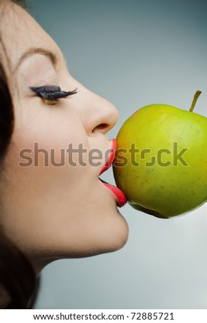 Closeup portrait of a lovely young girl kissing a green apple standing on half-face against blue background