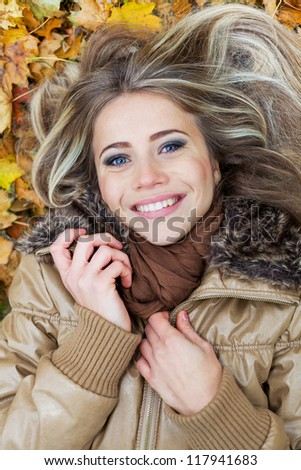 Closeup portrait of a nice young woman surrounded by autumn leaves
