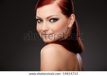 Closeup portrait of a redhead female model on grey background