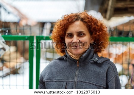 Closeup portrait of a redhead woman in the countryside during winter #1012875010