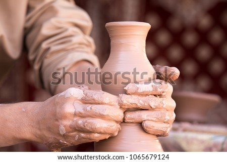 Closeup portrait of a sculptor's hands doing pottery on a clay wheel. Nizwa, Oman.