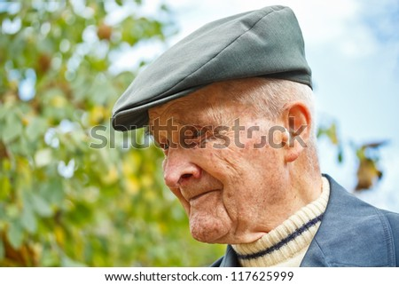 Closeup portrait of a senior man with hat - stock photo
