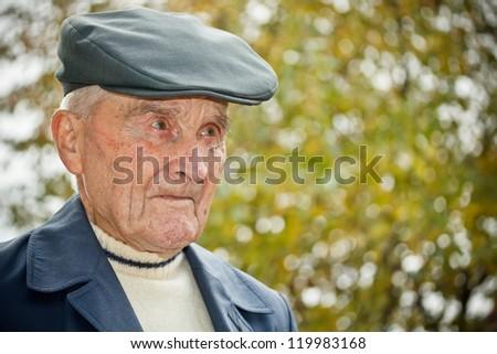 Closeup portrait of a senior man with hat - stock photo