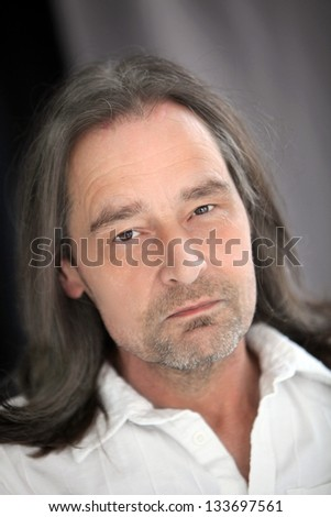 Closeup portrait of a serious handsome middle-aged unshaven man with long shoulder length hair