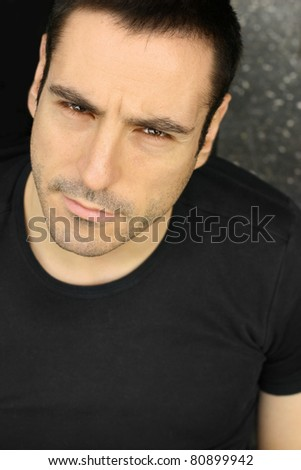 Closeup portrait of a serious man making expression in black shirt