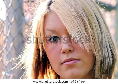 Closeup portrait of a serious young blond woman, taken outdoors.  Horizontal format.