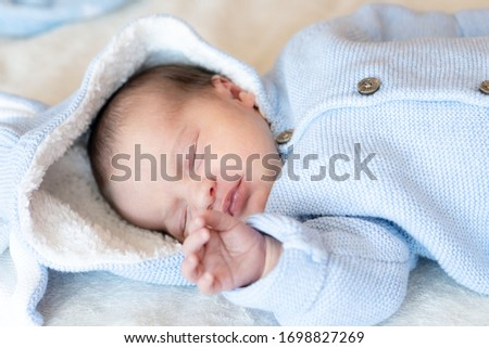 Closeup portrait of a sleeping newborn baby. Newborn wearing a warm blue jacket with toy bunny ears sleeping on blanket in sunny nursery.