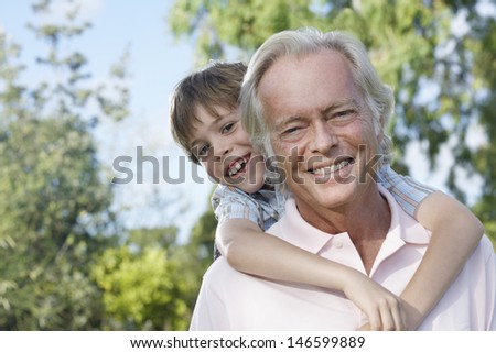 Closeup portrait of a smiling grandfather with grandson riding piggyback outdoors