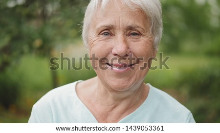 Closeup portrait of a smiling gray-haired old woman on nature
