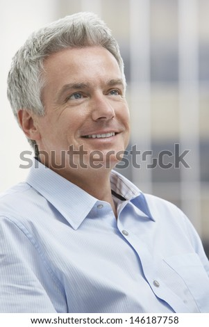 Closeup portrait of a smiling middle aged businessman looking up