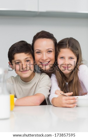 Closeup portrait of a smiling mother with young kids in the kitchen at home