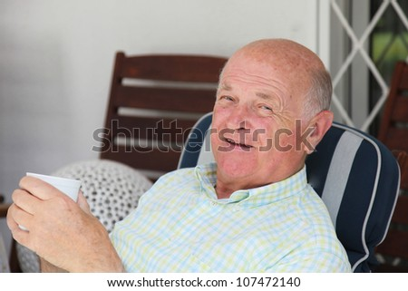 Closeup portrait of a smiling relaxed elderly man enjoying a cup of tea