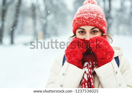closeup portrait of a smiling woman in warm clothes, red knitted cap, scarf and mittens walking on the snowy street under falling snowflakes after blizzard in city. Happy woman playing with the snow #1237536025