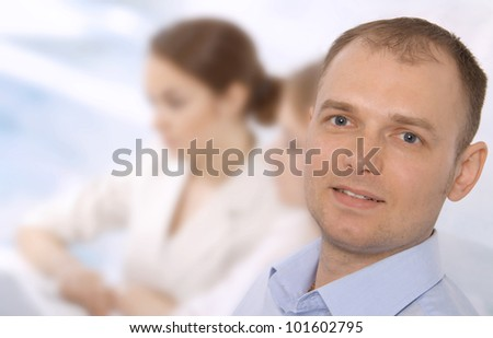 Closeup portrait of a smiling young business executive in a meeting with colleagues