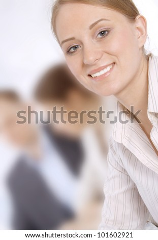 Closeup portrait of a smiling young business woman in a meeting with colleagues
