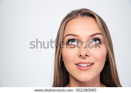 Closeup portrait of a smiling young woman looking up isolated on a white background
