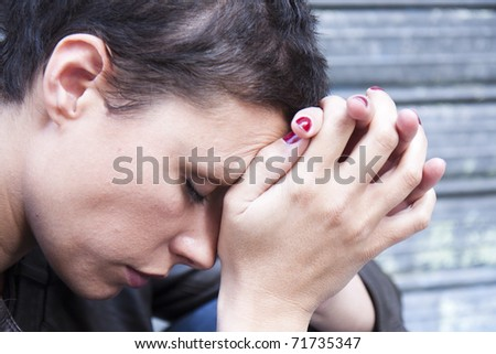 Closeup portrait of a stressed woman in a deep pain. Her face is pressed against her hands.