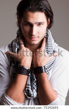 closeup portrait of a stylish young man with a scarf with piercings and bangles
