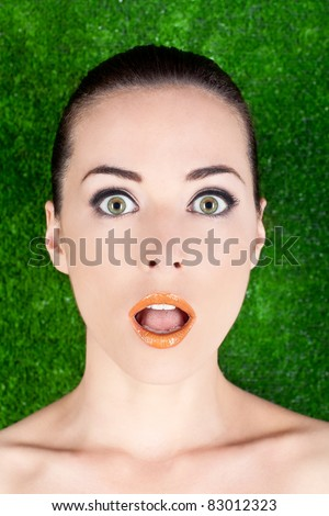 Closeup portrait of a surprised beautiful woman mouth open on green - stock photo