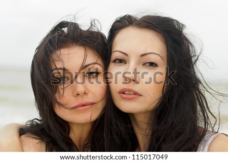 Closeup portrait of a two young women on the beach